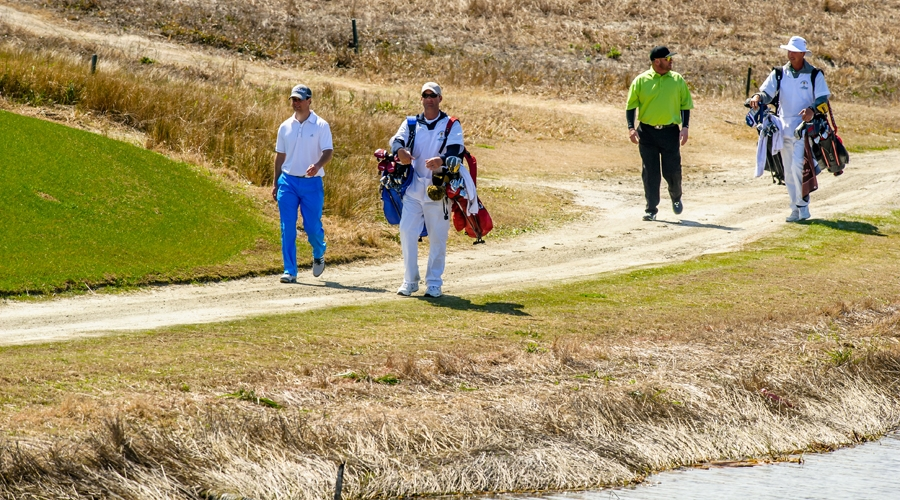 2014 friendship cup players and caddies walk along the golf course