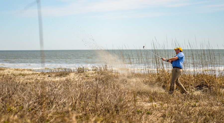 Friendship cup player hits a sand shot on the ocean course.