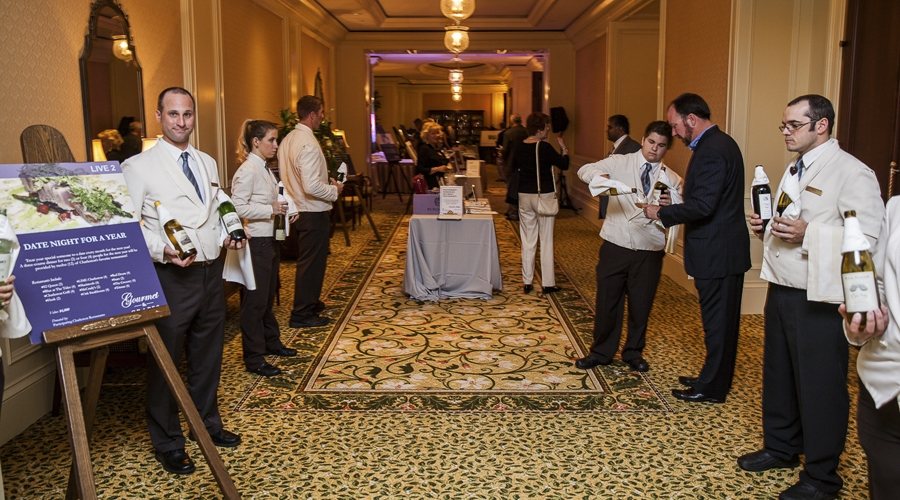 Servers pouring wine at the annual gourmet and grapes weekend