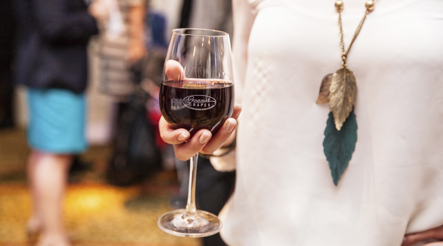 Guest holding glass of wine at annual gourmet and grapes weekend
