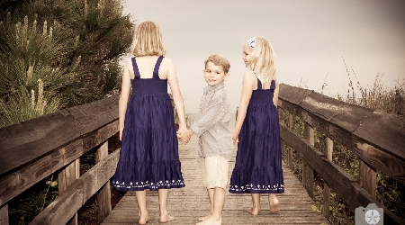 Children post for portrait on beach boardwalk by photographics