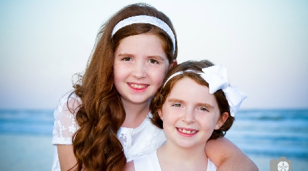 Young sisters pose for photo at kiawah island beach by photographics