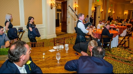 Bagpipe player leads jacket presenters into room