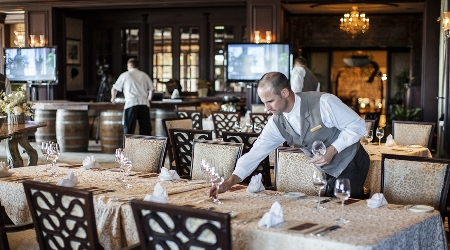Server sets table at the ocean room at the sanctuary