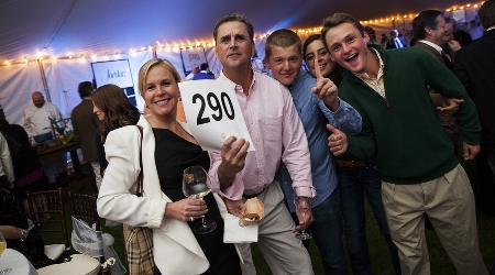 Guests holding their auction number at the annual gourmet and grapes weekend