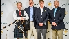 Golfers with bagpipe player post for photo