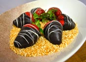 Six fresh strawberries coated in dark chocolate and garnished with chocolate, served atop caramelized croquant in a chocolate sprayed bowl