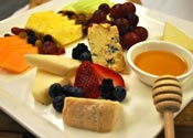 Mixed arrangement of fresh fruits, nuts, and artisanal cheeses