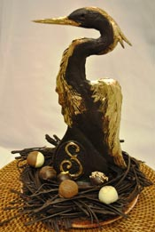 A solid chocolate heron standing 2.5 feet tall with a milk chocolate nest containing an assortment of chocolate truffles and rochers