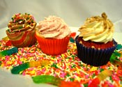 Three gourmet cupcakes decorated in a whimsical style and childhood favorite candies; gummy worms and sprinkles.