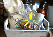 A basket containing Jasmine Porch Signature Peach BBQ sauce, Geechie Boy Mill White Grits and House Pecan Pralines